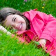 Happy cute child lying in a grass of a flower garden — Stock Photo