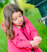 Little girl drinking water in a fountain — Stock Photo
