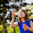 Beautiful child blowing bubbles — Stock Photo #26471183