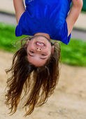 Beautiful child hanging upside and laughing — Stock Photo
