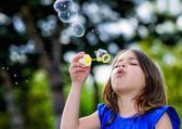 Beautiful child blowing bubbles — Stock Photo