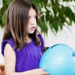 Portrait of very cute girl playing with a blue balloon — Stock Photo