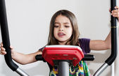 Porträt einer schönen jungen girlr unning auf eine elliptische fahrrad — Stockfoto