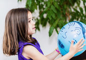 Portrait of pretty young girl child playing with a blue balloon — Stock Photo