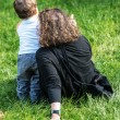 Woman sitting on the grass pointing something to her very young son standing next to her — Stock Photo #35078413
