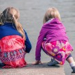 Two young girls squatting at the water's edge — Stock Photo