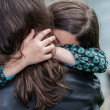 Stock Photo: Expressive portrait of pretty girl hugging her mother