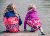 Two young girls squatting at the water's edge — Photo