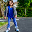 Stock Photo: Pretty little girl doing rollerblade in street