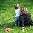 Woman sitting on the grass pointing something to her very young son standing next to her — Stock Photo #35081355