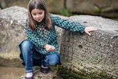 Pretty little girl playing on a rock at the water's edge — Stock Photo