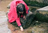 хорошенькая девочка, играя на скале у кромки воды — Стоковое фото