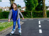 Pretty little girl doing rollerblade in the street — Stock Photo