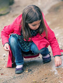 Pretty little girl playing at the water's edge — Stock Photo