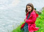 Natural portrait of cute child with greenery and water in the background — Stock Photo