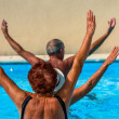 Active seniors getting a workout at the swimming pool — Stok fotoğraf