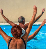 Active seniors getting a workout at the swimming pool — Stock Photo