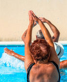 Active seniors getting a workout at the swimming pool — Stock fotografie