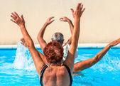 Activas mayores a una rutina de ejercicios en la piscina — Foto de Stock