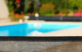 Barrier for the safety of children with a pool in the background — Stock Photo