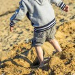 Young child playing in the sand at the seaside — Stock Photo