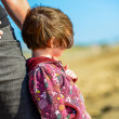 Young child tight against her mother watching the sea beyond — Stock Photo