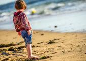 Один милый ребенок, стоя перед океаном — Стоковое фото