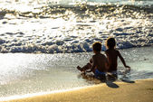 Two young children sitting in the waves of the ocean under a beautiful sunset — Stock Photo