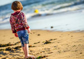 One young cute child standing in front of the ocean — Stock Photo