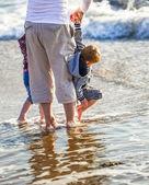 Två barn och deras pappa spela framför havet — Stockfoto