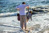 Dois filhos e seu pai joga em frente ao oceano — Fotografia Stock