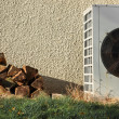 Stock Photo: Pile of firewood and Airconditioning near wall