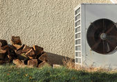 Pile of firewood and Airconditioning near a wall — Stock Photo