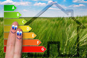 Cute diagram of house energy efficiency rating with two cute happy fingers and green background — Stockfoto