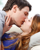 Attractive couple of lovers kissing itself lovingly on a sofa — Stock Photo