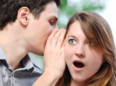 Man whispering in the ear of his surprised wife — Stock Photo