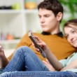 Beautiful woman watching tv while her lover is watching a screen of cell — Stock Photo #42224687