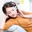 Beautiful relaxed young woman listening of the music by being lengthened on her sofa — Stock Photo