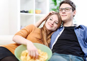Relaxed young couple watching television in their living room — Stock Photo