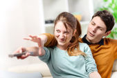 Beautiful couple bickering to change tv channel on remote control — Stock Photo