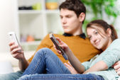 Beautiful woman watching tv while her lover is watching a screen of cell — Stock Photo