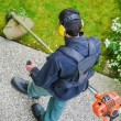 Gardener using corded string trimmer in a park — Stock Photo #44271125