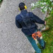 Gardener using corded string trimmer in a park — Stock Photo #44271679