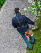 Gardener using corded string trimmer in a park — Stock Photo