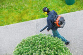 Gardener using a gas blower in a park — Stock Photo
