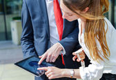 Junior executives consulting a touchpad in front of their company — Stock Photo