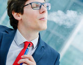 Pretty single man inhaling from an electronic cigarette — Stock Photo