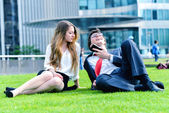 Successful Junior executives dynamics laying down on green grass — Stock Photo