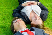 Successful Junior executives dynamics lying on grass — Stock Photo