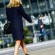 Young business woman walking on the city street — Stock Photo #46418637